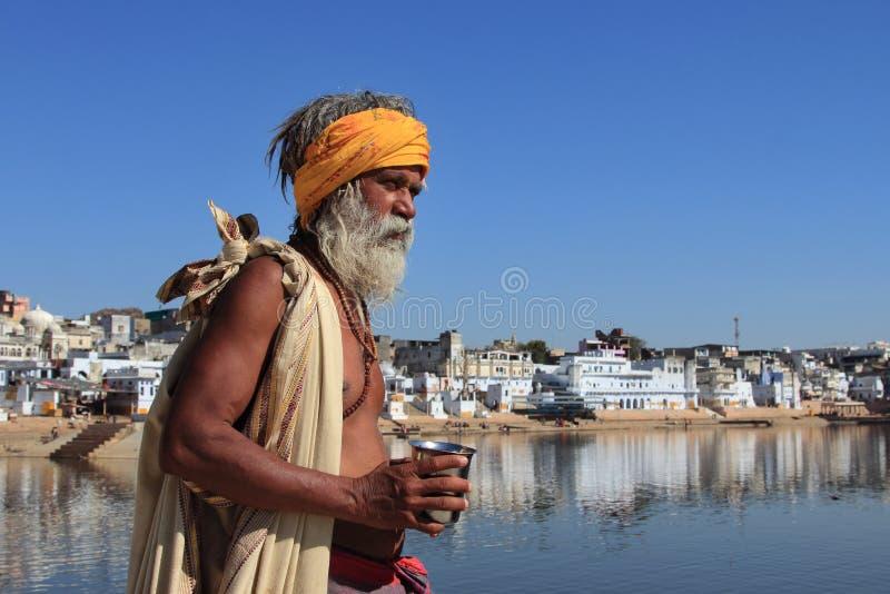 L'homme de Sadhu se tient aux banques du lac Pushkar image stock