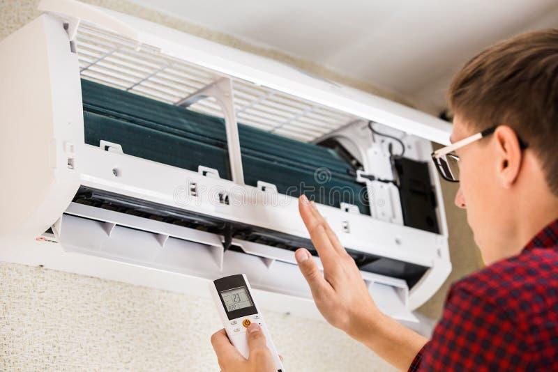 L'homme de service est entretien de climatiseur photographie stock libre de droits