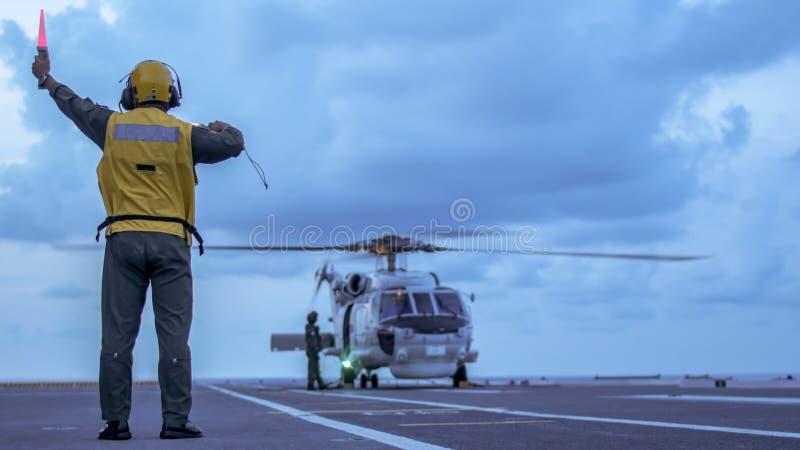 L'homme de signal donnent un signal à l'hélicoptère de guerre sous-marine photo stock