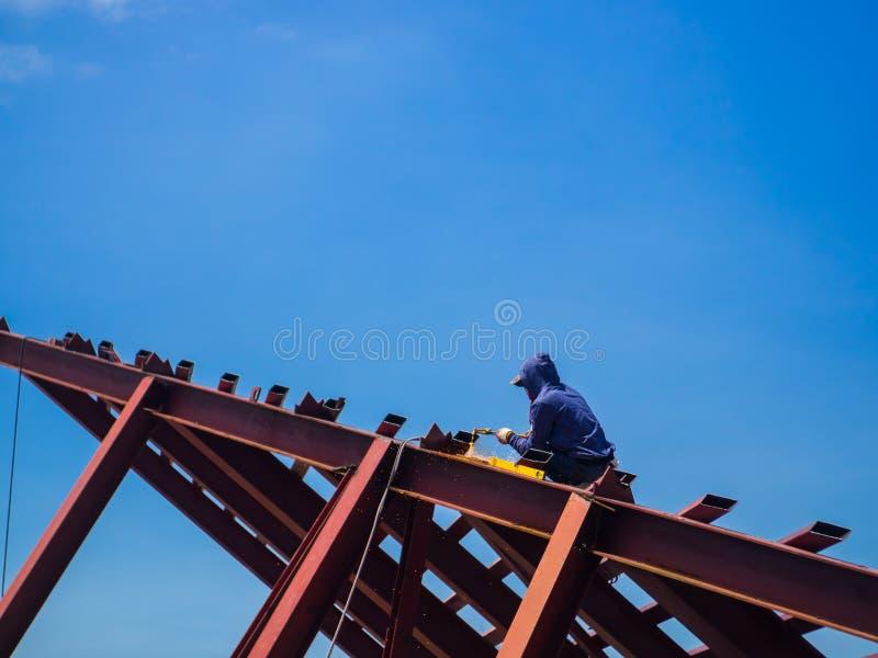 L'homme de soudeuse une soudure le toit en acier, travailleur avec non protégé photos stock