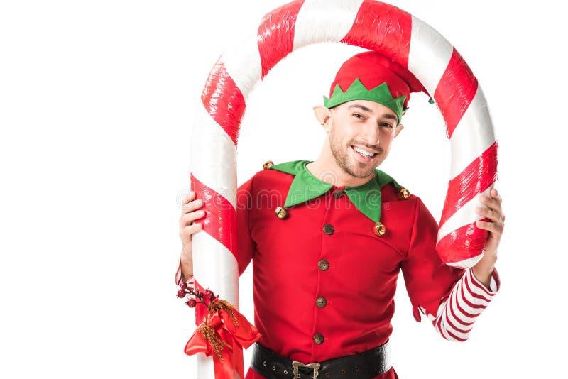 l'homme de sourire dans la position de costume d'elfe de Noël sous la grande canne de sucrerie a isolé images libres de droits