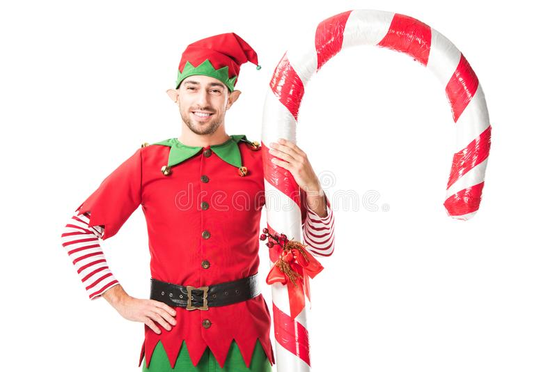 l'homme de sourire dans le costume d'elfe de Noël avec la main sur des hanches se tenant près de la grande canne de sucrerie a is photographie stock libre de droits