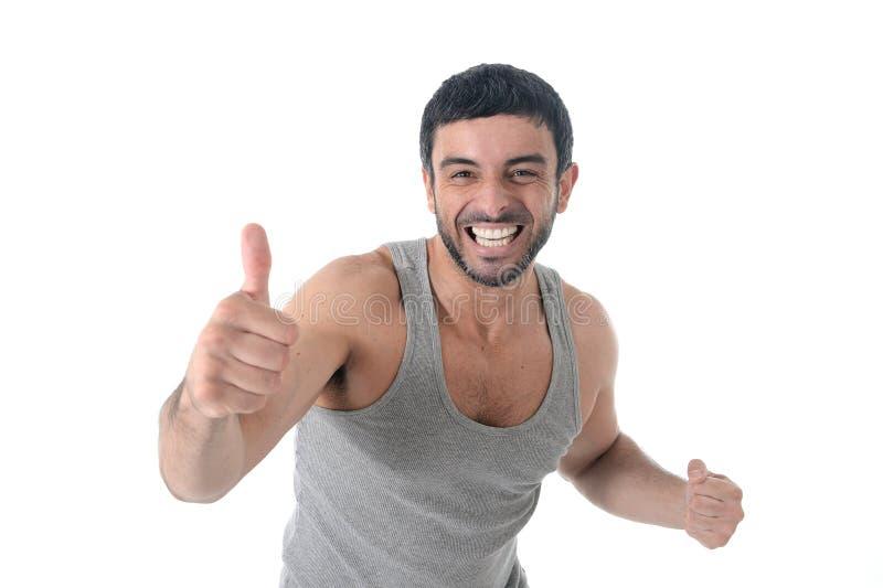 L'homme de sourire de sport avec la chemise courante donnant le pouce pour le centre de fitness ajoutent photographie stock
