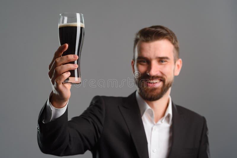 L'homme de sourire a soulevé son verre photo libre de droits