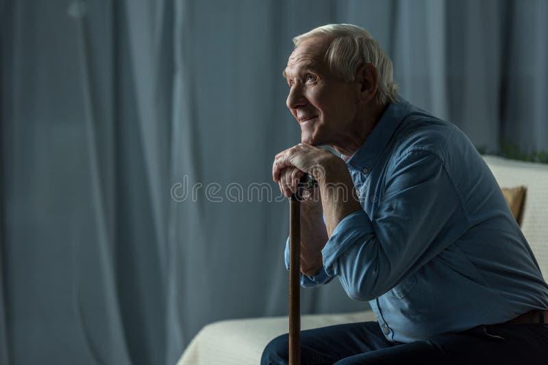 L'homme de sourire supérieur se penche sur une canne tout en se reposant images libres de droits