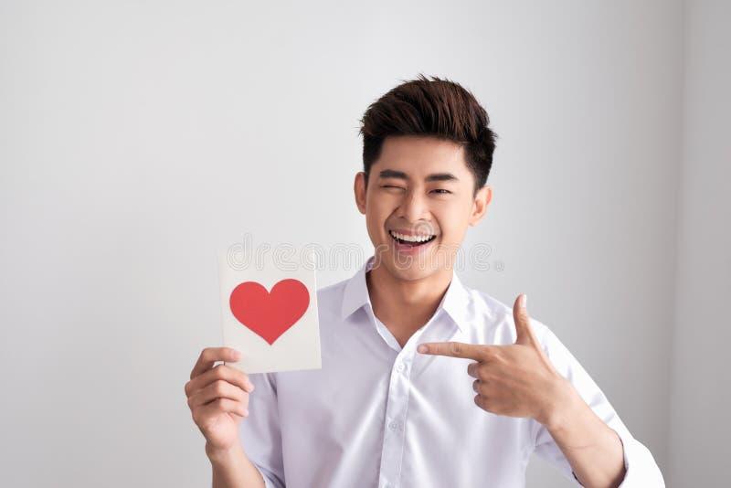 L'homme de sourire tenant le ` s de valentine cardent la position sur un fond blanc photos libres de droits