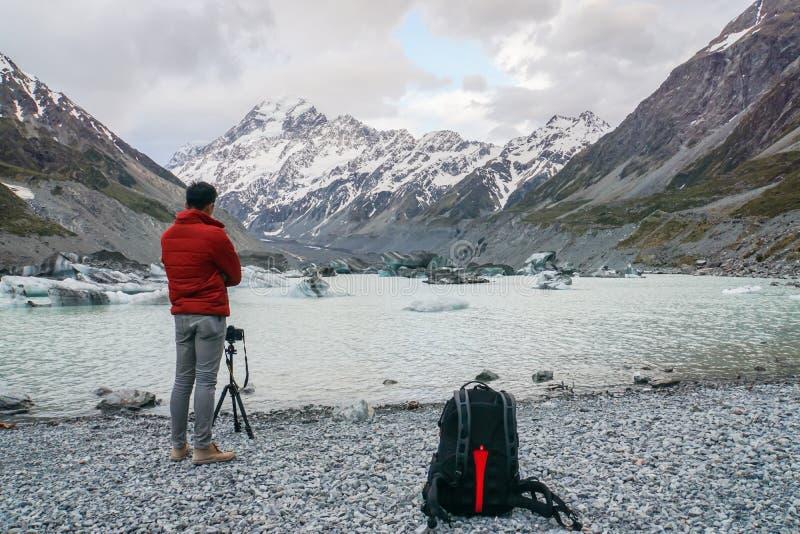 L'homme de touristes avec la veste prend la photo du cuisinier de bâti par l'appareil-photo de DSLR avec le trépied images libres de droits
