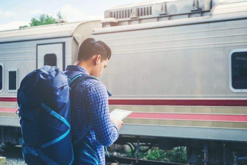 L'homme de voyageur à l'aide du comprimé et les attentes s'exercent sur la plate-forme ferroviaire photographie stock