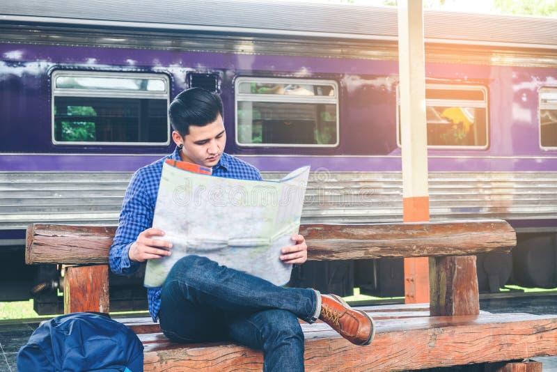 L'homme de voyageur avec la carte et les attentes s'exercent sur la plate-forme ferroviaire photo libre de droits