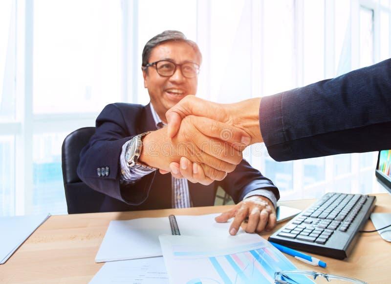 L'homme des affaires deux serrant la main avec émotion de bonheur après conviennent image stock