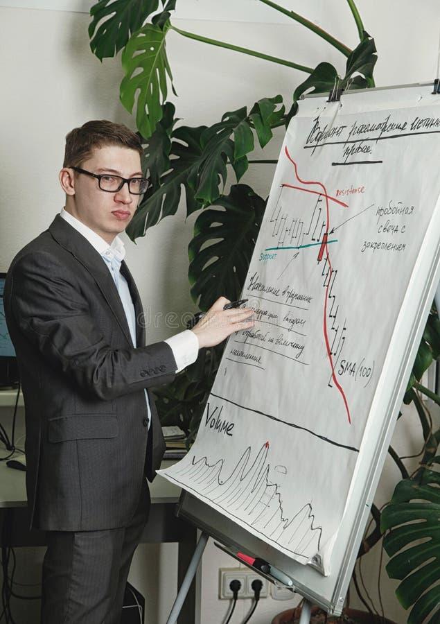 L'homme dessine les diagramms marchands sur le conseil de présentation de papper images stock