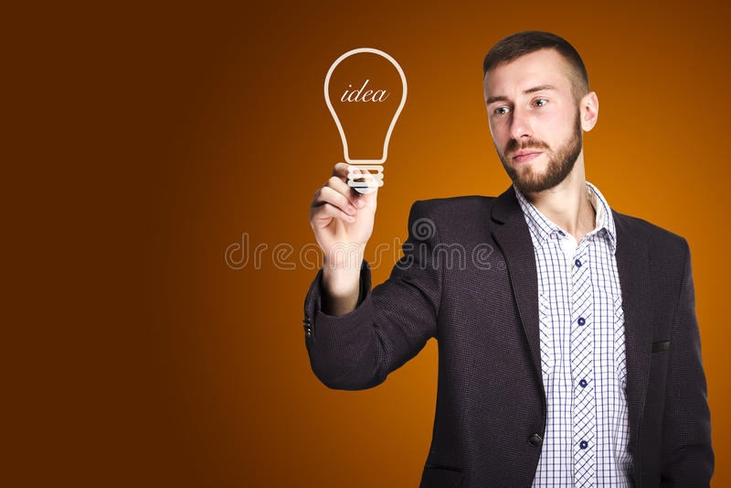 L'homme dessine une ampoule photo stock