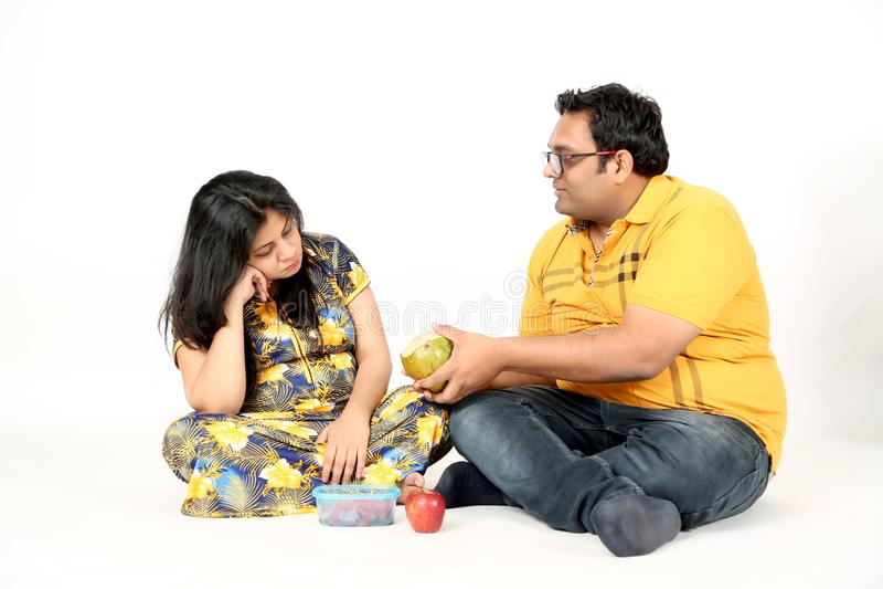 L'homme donne à l'eau de noix de coco la dame enceinte images stock