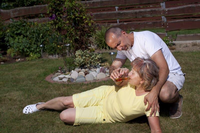 L'homme donne à femme avec l'épuisement dû à la chaleur quelque chose boire photo libre de droits