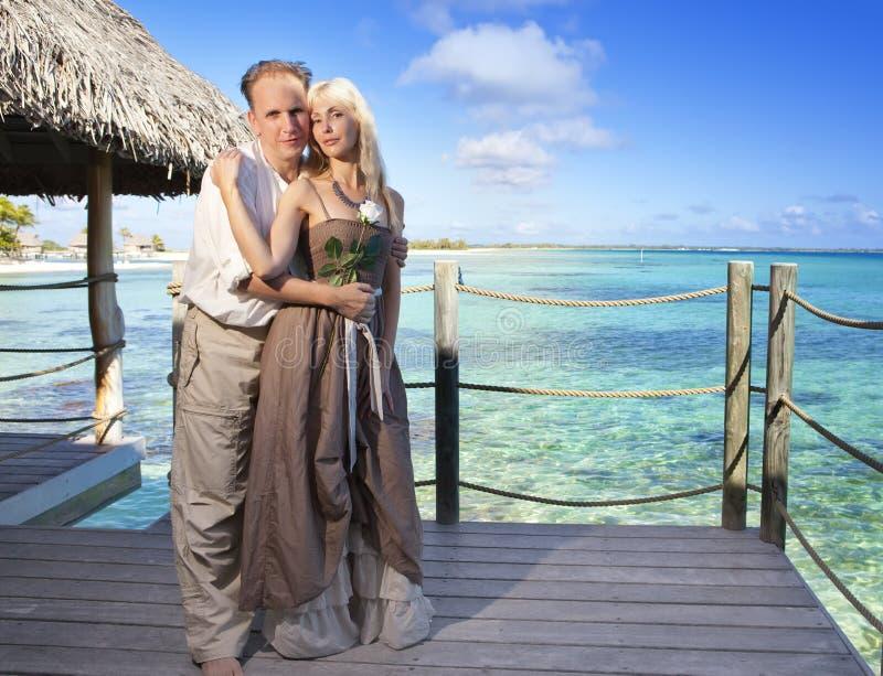 L'homme donne une rose à la femme sur le fond de mer de turquoise photo stock