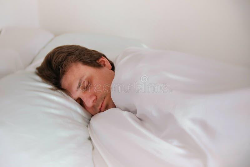 L'homme dort dans seul le lit sous la couverture Vue de côté images stock