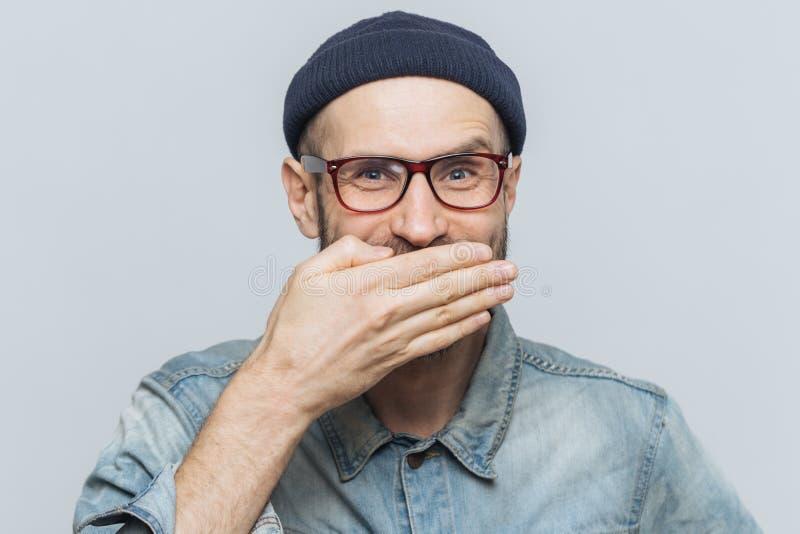 L'homme drôle avec le regard attrayant rit nerveusement ou rit joyeux, couvre la bouche de main, essaye d'arrêter des sentiments, photographie stock libre de droits
