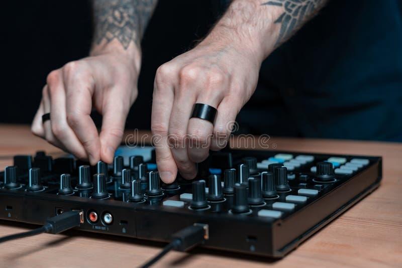 L'homme du DJ cr?e la musique ?lectronique dans le studio image stock