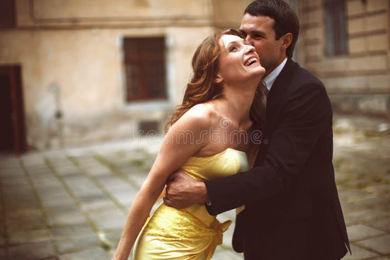 L'homme embrasse la dame dans la tête jaune tandis qu'elle s'appuie sur lui photo libre de droits