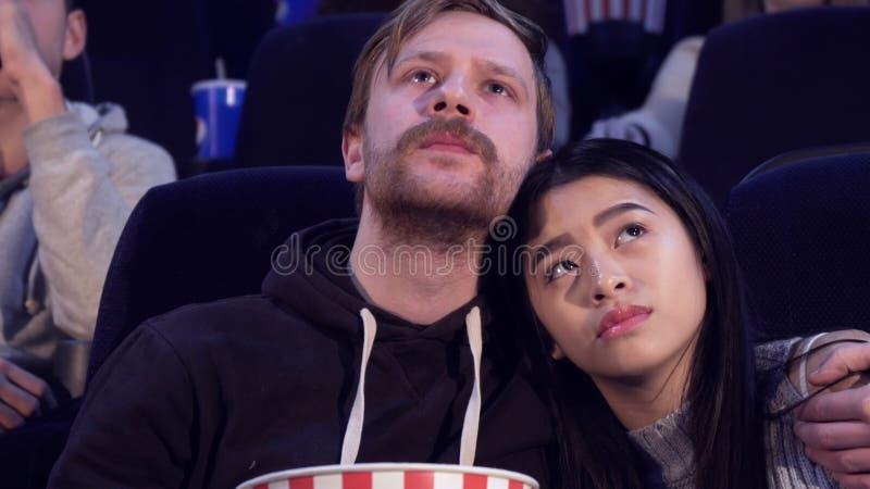 L'homme embrasse son amie à la salle de cinéma image libre de droits