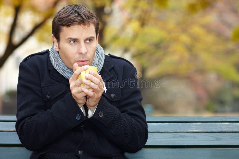 L'homme en automne boit du thé photographie stock