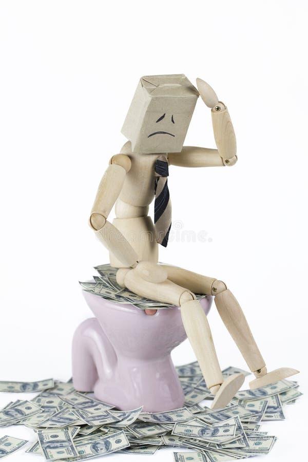 L'homme en bois a diminué se reposer sur la cuvette des toilettes remplie d'argent liquide images libres de droits