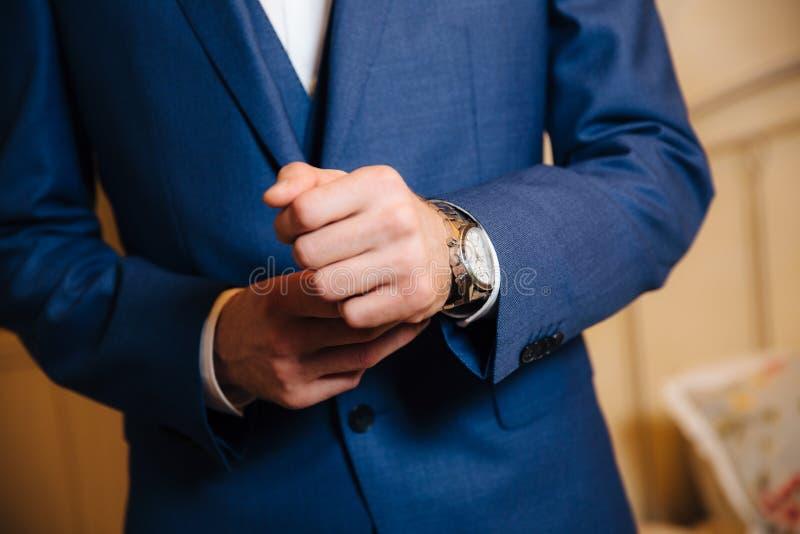 L'homme en gros plan met dessus une montre d'or avec une ceinture en cuir, homme d'affaires est habillé dans un costume élégant,  photos stock