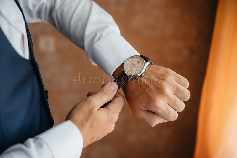L'homme en gros plan met dessus une montre d'or avec une ceinture en cuir, homme d'affaires est habillé dans un costume élégant,  photos libres de droits