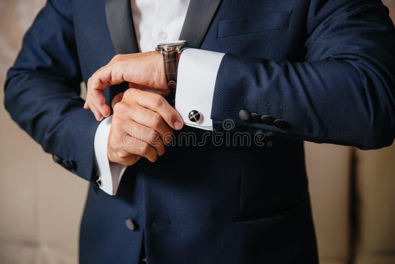 L'homme en gros plan met dessus une montre d'or avec une ceinture en cuir, homme d'affaires est habillé dans un costume élégant,  photo stock