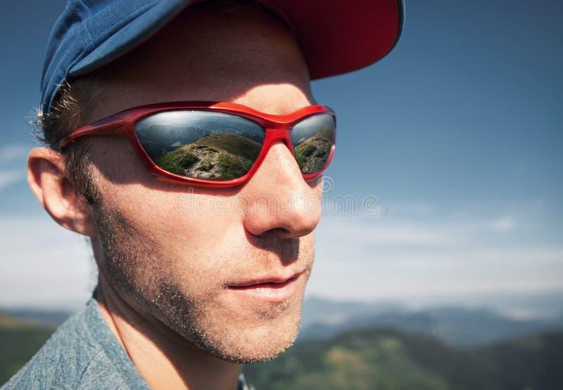 L'homme en verres de soleil avec la montagne mirorred dans elle photographie stock