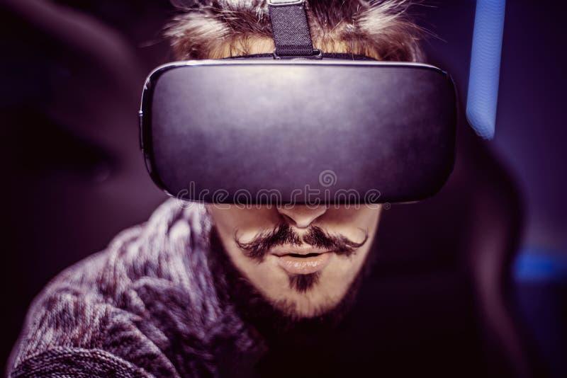 L'homme en verres virtuels observe un film dans 5d dans un cinéma image libre de droits