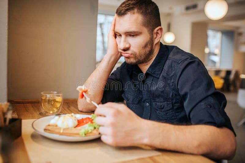 L'homme ennuyeux et triste s'assied à la table et au café Il tient un morceau de légume sur la fourchette L'homme le regarde et photos stock