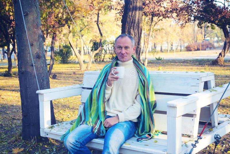 L'homme, enveloppé dans une couverture, boit du café photo libre de droits