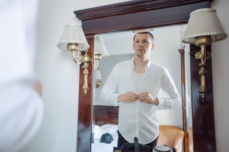 L'homme est chemise de blanc de habillage photo stock