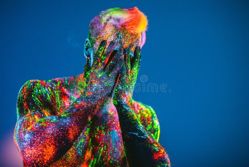 L'homme est d?cor? dans une poudre ultra-violette photographie stock