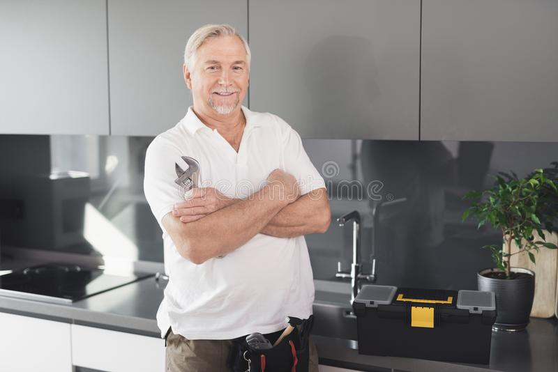 L'homme est dans la cuisine Il a une clé de chrome dans sa main À côté de lui est une boîte à outils photographie stock libre de droits