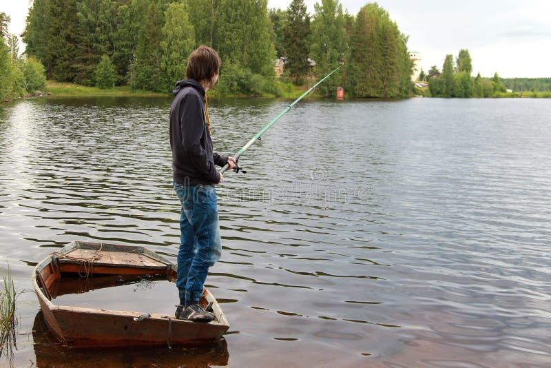 L'homme est pêche, se tenant dans un bateau complètement de l'eau photos stock
