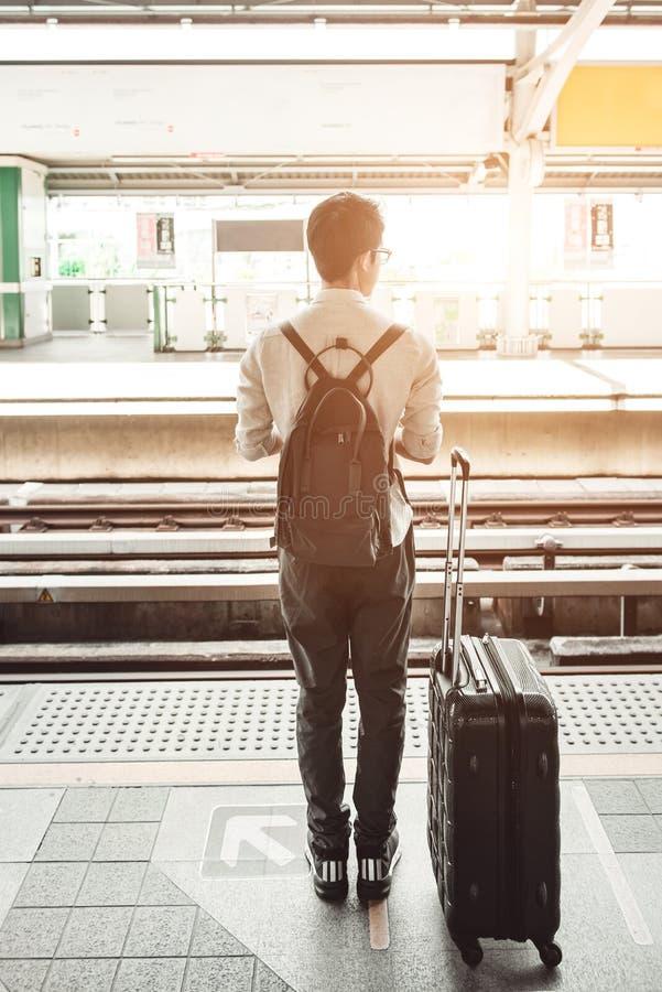 L'homme est sur la station de train avec le sac de voyage, utilisant le téléphone portable, photos stock