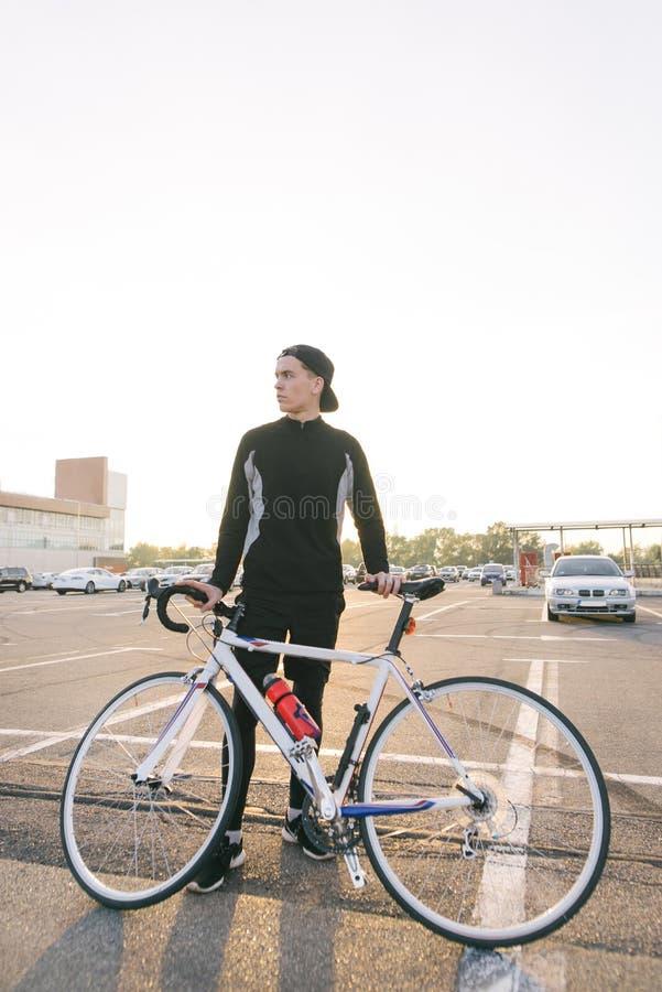 L'homme est un cycliste avec des vêtements de sport foncés et un chapeau avec une bicyclette sur le contexte du paysage de ville photographie stock libre de droits