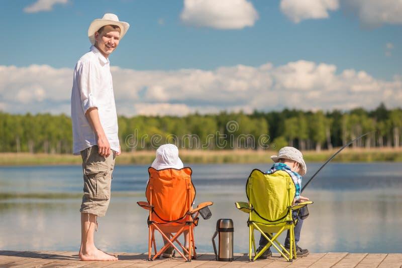 L'homme et deux fils sur la pêche, père enseigne des enfants photographie stock