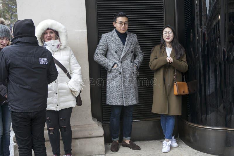 L'homme et la femme asiatiques se tiennent prêt la porte noire sous la voûte attendant la pluie sur le jardin de Covent photographie stock
