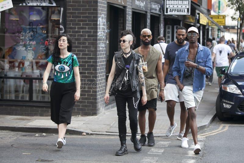 L'homme et la femme de hippie se sont habillés dans le style frais de Londonien marchant dans la ruelle de brique, une rue popula image libre de droits