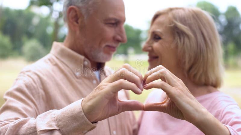 L'homme et la femme de sourire faisant des gestes le signe de coeur, se regardant, aiment se sentir image libre de droits