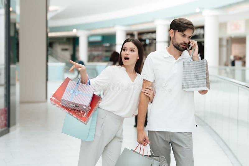 L'homme et la femme marchent dans le centre commercial La femme veut aller stocker mais l'homme est occupé à parler au téléphone photographie stock