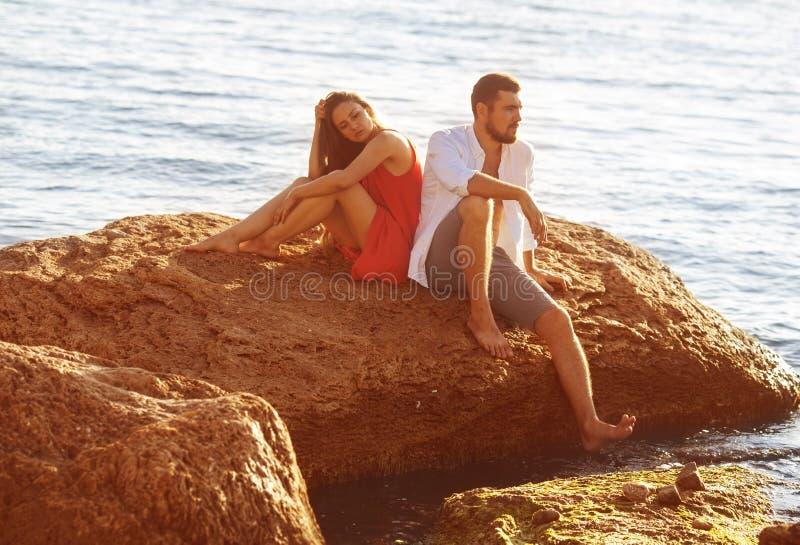 L'homme et la femme s'asseyent sur une pierre de peine image libre de droits