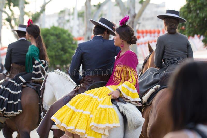 L'homme et la femme se sont habillés chez le cheval d'équitation traditionnel de costumes chez April Fair de la Séville photo stock