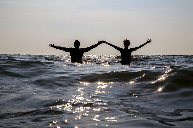 L'homme et la femme se tiennent en mer ayant jeté des mains, contre le soleil image libre de droits