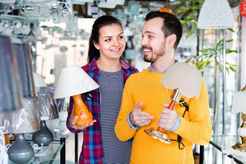 L'homme et la fille de sourire dans une boutique plus légère choisissent la lampe de bureau images libres de droits
