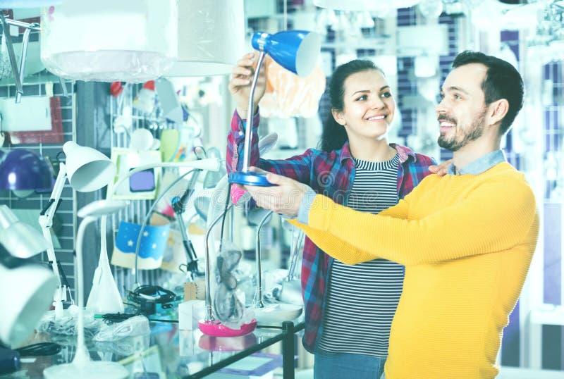 L'homme et la fille de sourire dans une boutique plus légère choisissent la lampe de bureau photos stock