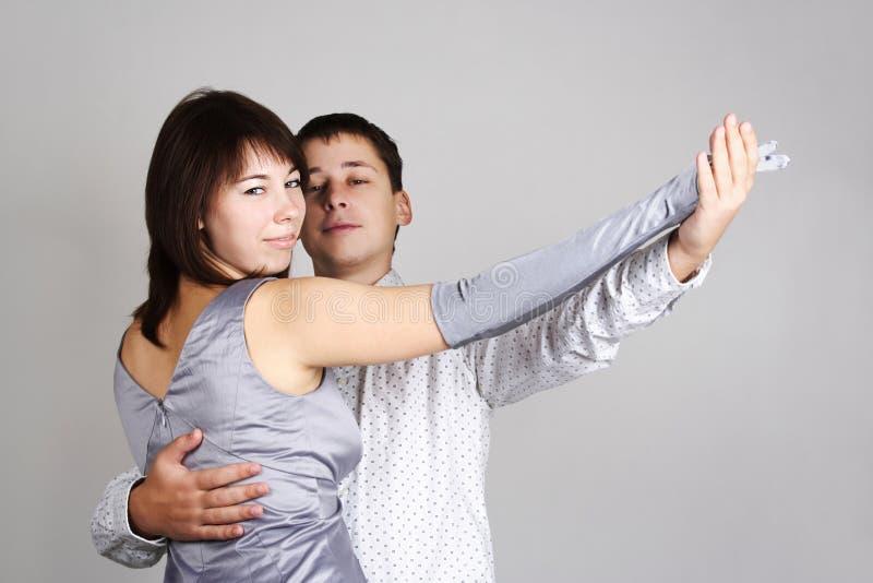 L'homme et le femme dans la danse argentée de robe valsent images stock
